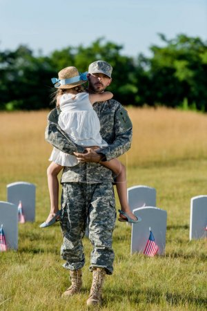 military father in cap holding in ams kid in straw hat near headstones with american flags