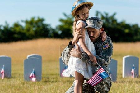 Photo pour Père militaire en uniforme étreignant l'enfant près des pierres tombales dans le cimetière - image libre de droit