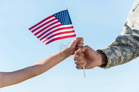 Photo pour Vue recadrée du père et de la fille militaires retenant le drapeau américain contre le ciel bleu - image libre de droit