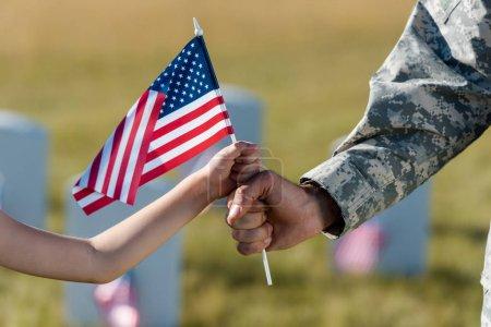 Photo pour Vue recadrée du père et de la fille militaires tenant le drapeau américain - image libre de droit