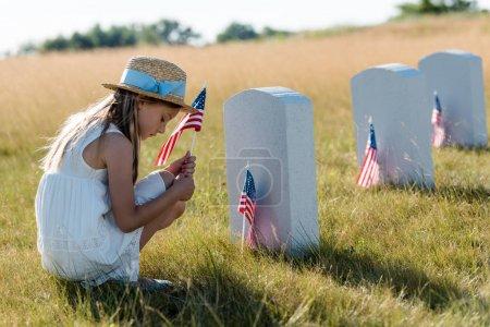 Foto de Niño triste en sombrero de paja sentado cerca de lápidas y la celebración de la bandera americana - Imagen libre de derechos