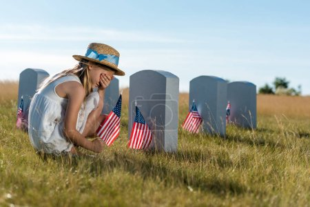 Photo for Kid in straw hat covering face while sitting near headstones with american flags - Royalty Free Image