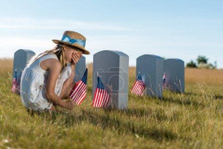 Foto de Niño en la cara de la cubierta del sombrero de paja mientras se sienta cerca de lápidas con banderas americanas - Imagen libre de derechos