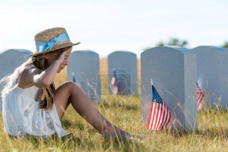 Photo pour Enfant en chapeau de paille touchant le visage tout en étant assis près des pierres tombales avec des drapeaux américains - image libre de droit