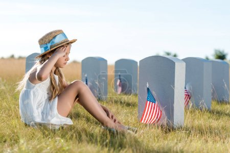 kid in straw hat giving salute while sitting near headstones with american flags
