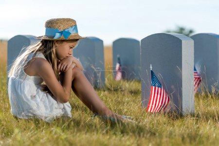 Foto de Enfoque selectivo de niño triste sentado y mirando las lápidas con banderas americanas - Imagen libre de derechos
