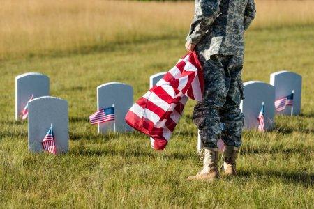 Photo pour Vue recadrée de l'homme dans l'uniforme militaire retenant le drapeau américain tout en restant dans le cimetière - image libre de droit
