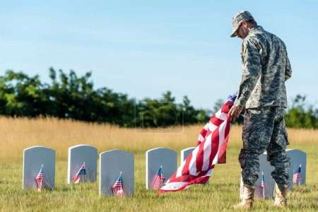 Foto de Soldado en uniforme y gorra sosteniendo la bandera americana en el cementerio - Imagen libre de derechos