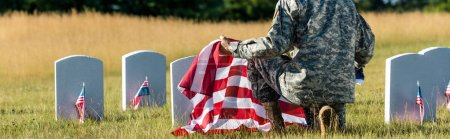panoramic shot of man in military uniform holding american flag while sitting in graveyard
