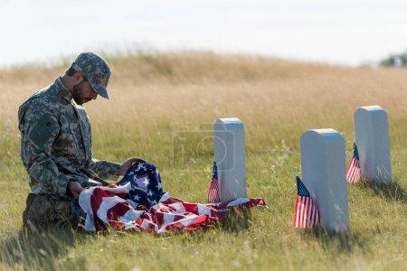 Foto de Triste soldado en uniforme de camuflaje y gorra sosteniendo la bandera americana mientras está sentado en el cementerio - Imagen libre de derechos