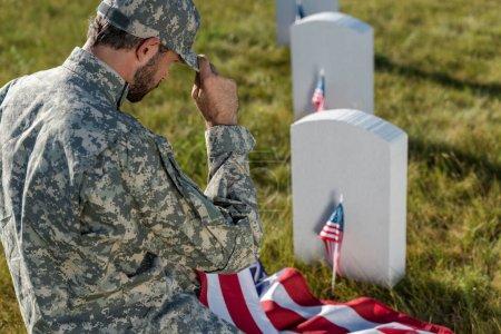 Foto de Enfoque selectivo del soldado en camuflaje uniforme tocando la tapa mientras está sentado en el cementerio - Imagen libre de derechos