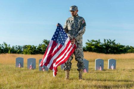 Foto de Guapo veterano en uniforme de camuflaje sosteniendo la bandera americana y de pie en el cementerio - Imagen libre de derechos