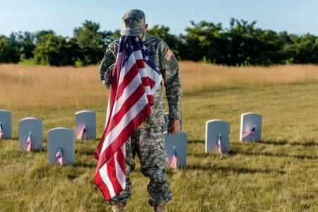 Foto de Soldado en camuflaje uniforme cubriendo la cara con la bandera americana y de pie en el cementerio - Imagen libre de derechos