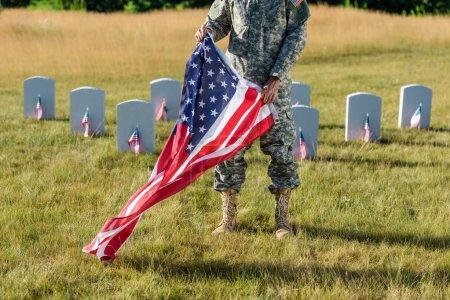 Photo pour Vue recadrée de l'homme dans l'uniforme de camouflage retenant le drapeau américain et restant dans le cimetière - image libre de droit