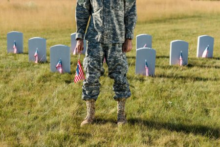 Foto de Vista recortada de veterano en uniforme de camuflaje con bandera americana y de pie en el cementerio - Imagen libre de derechos