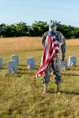 Photo for Veteran in camouflage uniform covering face with american flag and standing in graveyard - Royalty Free Image
