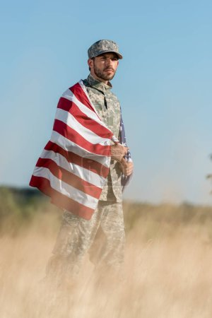 Photo pour Selective focus of man in camouflage uniform and cap holding american flag in golden field - image libre de droit