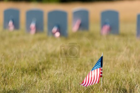 selective focus of american flag with stars and stripes near gravestones