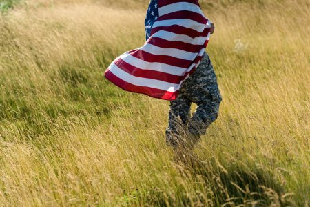 Photo for Cropped view of soldier in camouflage uniform holding american flag in field - Royalty Free Image