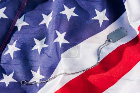 Photo pour Insigne métallique sur la chaîne près du drapeau américain avec des étoiles et des rayures - image libre de droit