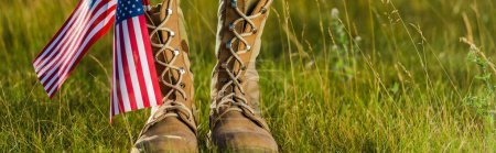panoramic shot of military boots near american flag with stars and stripes on grass