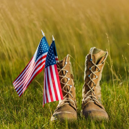Photo for Close up of military boots near american flag with stars and stripes on grass - Royalty Free Image