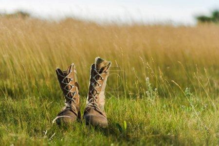 Photo pour Mise au point sélective des bottes militaires sur l'herbe verte - image libre de droit