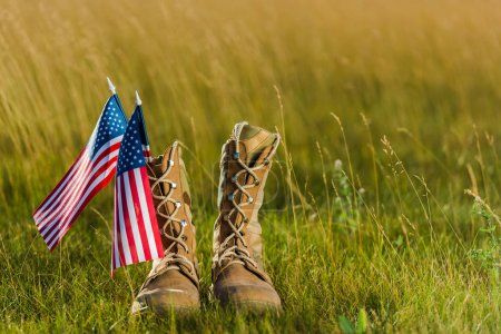 Photo for Military boots near american flag with stars and stripes on grass - Royalty Free Image