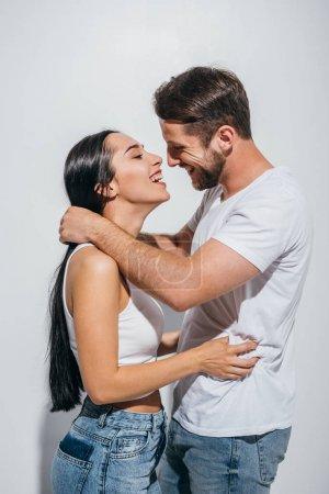 Foto de Vista lateral de la pareja joven abrazando mientras sonriendo y mirando el uno al otro - Imagen libre de derechos