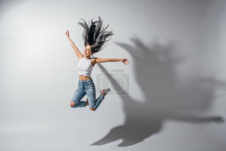 Photo for Full length view of excited girl jumping with hands in air - Royalty Free Image