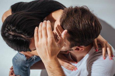 Foto de Vista superior de la pareja joven besándose mientras el hombre ocultando caras con la mano - Imagen libre de derechos