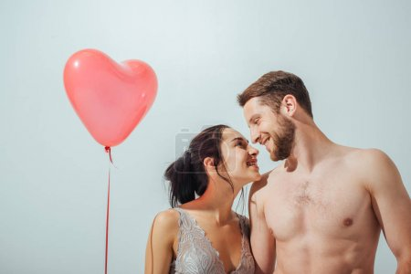 shirtless couple smiling and looking at each other while girl holding red balloon