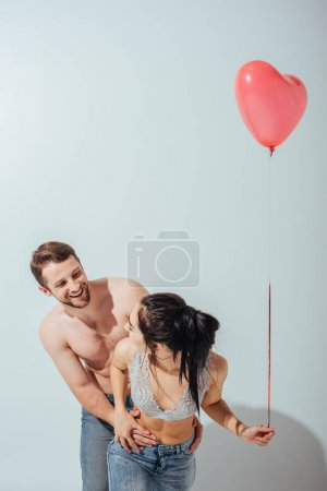 Photo for Sexy couple playing with each other and laughing while girl holding balloon in heart form - Royalty Free Image