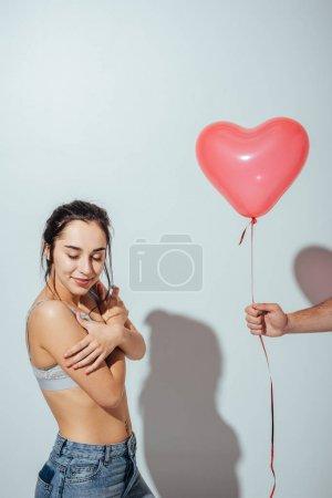 Photo pour Vue recadrée de l'homme donnant le ballon rouge sous forme de coeur à la fille attirante qui se tenant avec les yeux fermés - image libre de droit