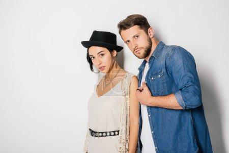 Photo pour Bel homme et belle fille dans des vêtements à la mode regardant l'appareil-photo sur le blanc - image libre de droit