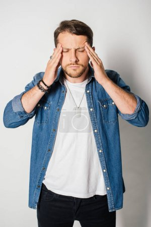 young man in stylish clothes with closed eyes and headache holding head