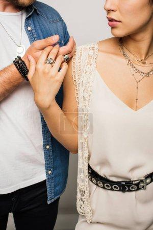 Photo pour Vue recadrée de couples dans les mains de fixation élégantes de vêtements - image libre de droit