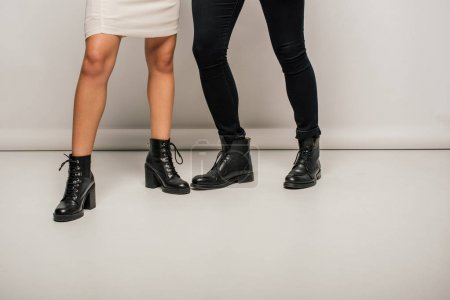 Photo for Cropped view of couple in fashionable clothes standing in black boots - Royalty Free Image