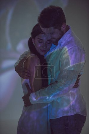 Photo for Beautiful couple hugging while standing in light from projector - Royalty Free Image
