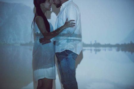 Photo pour Vue recadrée de couples dans l'amour étreignant tout en restant dans l'obscurité et en regardant les uns les autres - image libre de droit