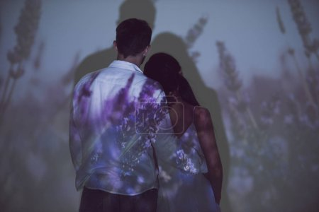 Photo for Back view of girl and man hugging while standing in darkness on light of projector - Royalty Free Image