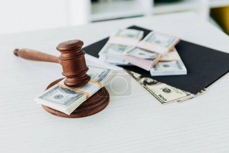 Photo pour Orientation sélective du marteau du juge près des billets en dollars sur la table - image libre de droit
