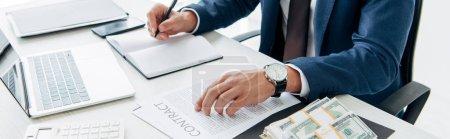 Photo pour Plan panoramique de l'homme en costume écrit dans un carnet près d'un ordinateur portable, de l'argent et des contrats - image libre de droit