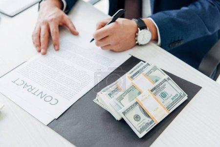 Photo pour Vue recadrée de stylo de fixation d'homme d'affaires près du contrat et de l'argent dans le bureau - image libre de droit