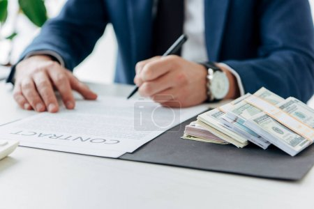 Photo for Selective focus of money near businessman signing contract in office - Royalty Free Image