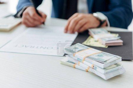 Photo pour Orientation sélective des billets de banque en dollars près de contrat de signature d'homme d'affaires dans le bureau - image libre de droit