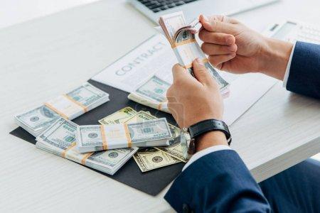 Photo pour Vue recadrée de l'homme d'affaires comptant les billets en dollars dans le bureau - image libre de droit