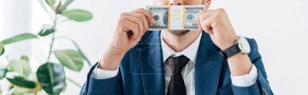 Photo pour Plan panoramique de l'homme couvrant le visage tout en sentant les billets en dollars - image libre de droit
