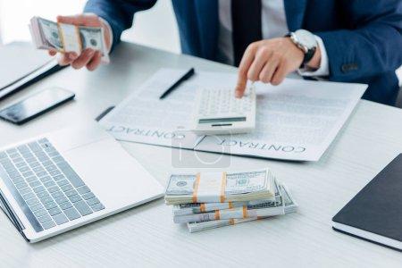Foto de Vista recortada del hombre de negocios usando calculadora y la celebración de dinero cerca del contrato - Imagen libre de derechos