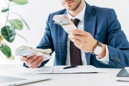 Photo pour Orientation sélective de l'homme d'affaires tenant des billets de banque en dollars près du contrat - image libre de droit